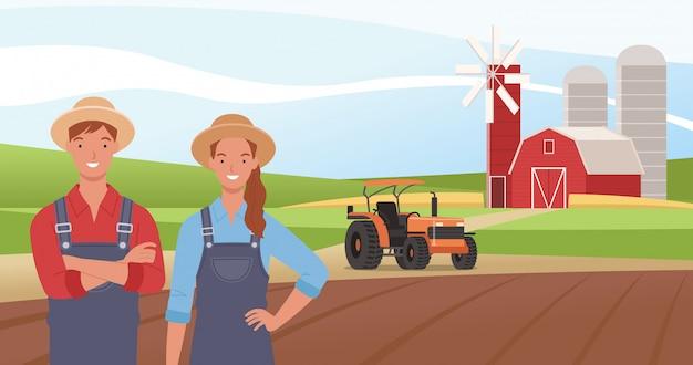 Felice coppia di agricoltori sullo sfondo del campo, fienile e trattore.