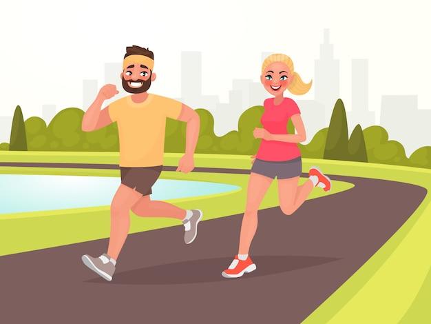Coppie felici che vanno in giro nel parco. l'uomo e la donna sono impegnati nel fitness