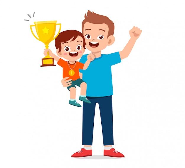 Il ragazzo felice del bambino sveglio diventa il primo vincitore