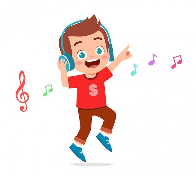 Il ragazzo sveglio felice del bambino ascolta musica