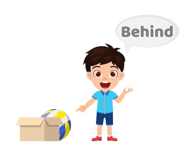 Felice ragazzo carino bambino con palla e cartone, apprendimento concetto di preposizione, tra preposizione e puntamento isolato