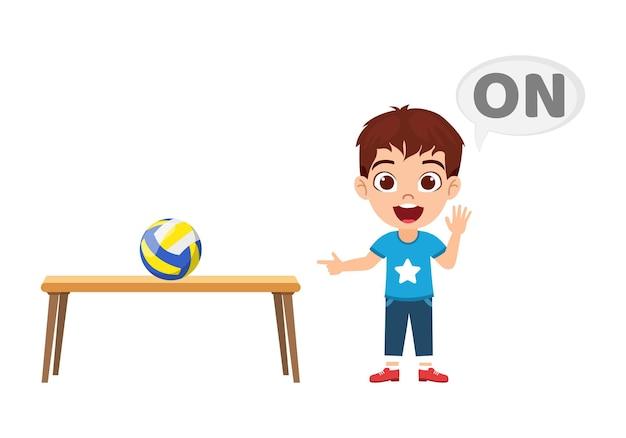 Felice ragazzo carino bambino con palla e tavolo, apprendimento concetto di preposizione, su preposizione e puntamento