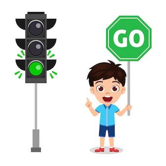 Ragazzo sveglio felice del bambino con la tenuta del segnale stradale va il segnale stradale isolato su fondo bianco
