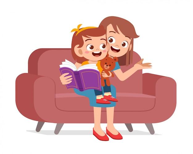 La ragazza sveglia felice del bambino ha letto il libro con la mamma
