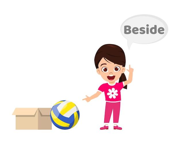 Felice ragazza carina bambino con palla e cartone, apprendimento concetto di preposizione, accanto alla preposizione e puntamento isolato