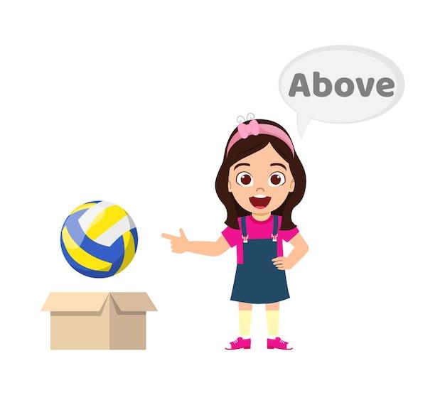 Ragazza sveglia felice del bambino con la palla e il cartone, concetto di preposizione di apprendimento, sopra la preposizione e posa isolata