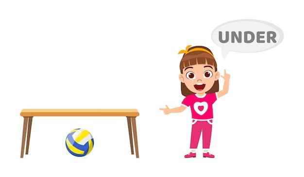 Felice ragazza carina bambino con palla e tavolo, apprendimento concetto di preposizione, sotto preposizione e puntamento isolato