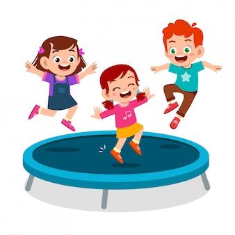Il sorriso felice del bambino sveglio salta sul trampolino