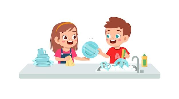 Felice carino piccolo ragazzo e ragazza che lavano il piatto insieme