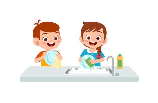 Felice carino piccolo ragazzo e ragazza che lavano il piatto insieme Vettore Premium