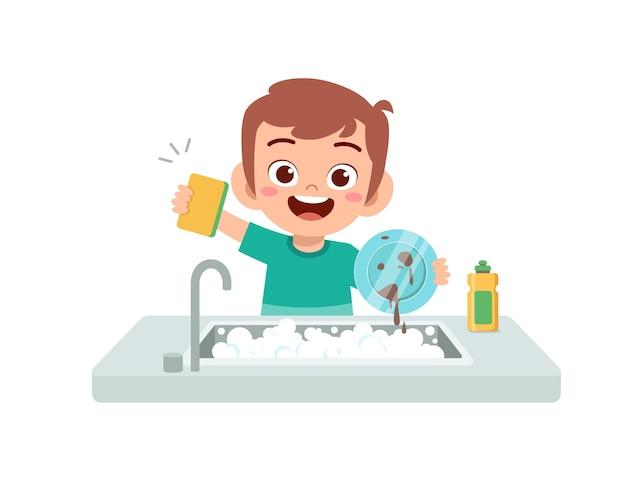 Felice carino ragazzino lavare il piatto in cucina