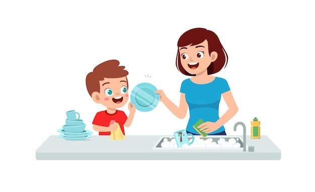 Piatto di lavaggio del ragazzino sveglio felice con la madre