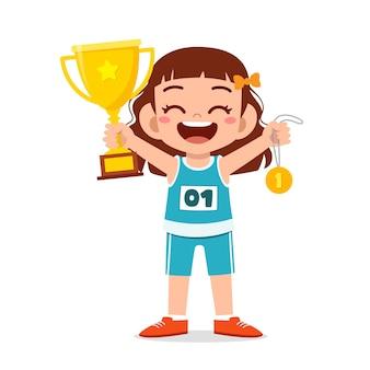 Felice carino bambina tenendo la medaglia d'oro e il trofeo