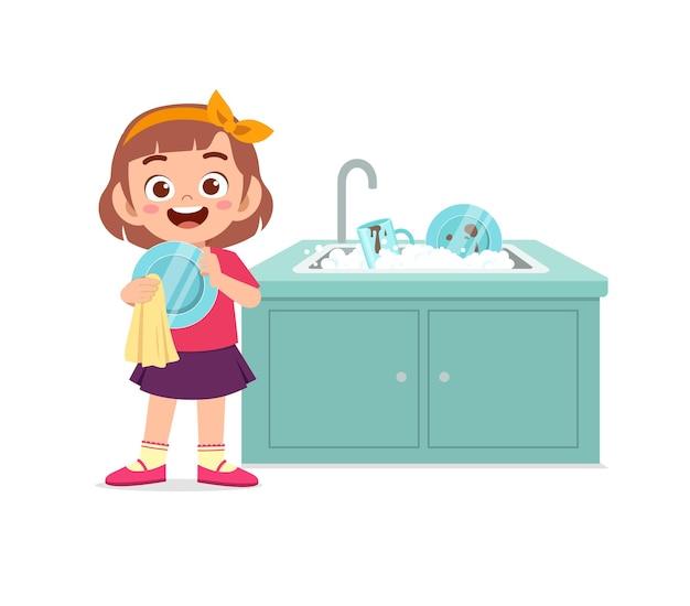Bambina sveglia felice che lava il piatto in cucina