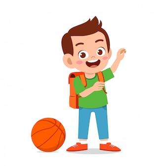 Il ragazzo sveglio felice del bambino gioca a pallacanestro