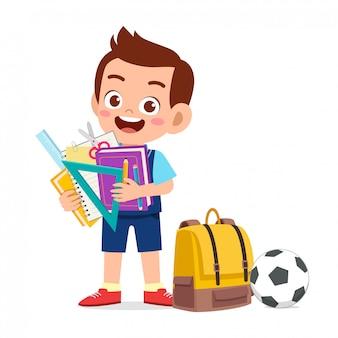 Il ragazzo sveglio felice del bambino prepara per la scuola