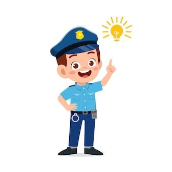 Felice e carino ragazzino che indossa l'uniforme della polizia e pensa con il segno della lampadina