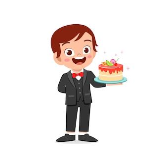 Felice carino ragazzino ragazzo che indossa l'uniforme del cameriere e tenendo la torta di compleanno