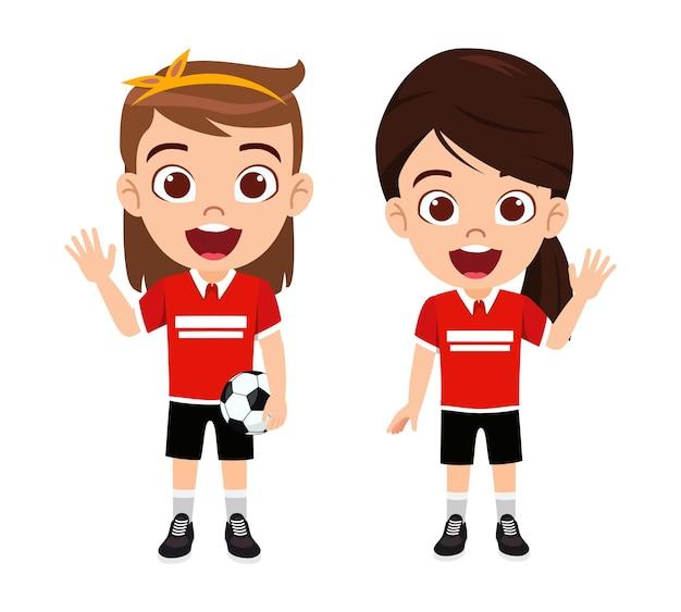 Carattere sveglio felice delle ragazze del ragazzino che ondeggia e che tiene il calcio con la bella maglia rossa con l'espressione allegra isolata