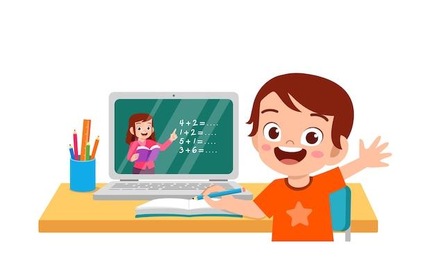 Il ragazzino sveglio felice fa la scuola a casa con il laptop del computer connesso all'e-learning e al corso di studio su internet.