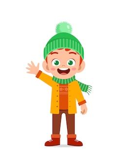 Felice carino ragazzino gioca e indossa la giacca nella stagione invernale