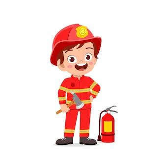 Ragazzino sveglio felice che indossa l'uniforme del pompiere e che tiene l'ascia