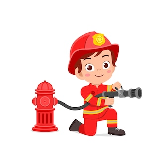 Ragazzino sveglio felice che indossa l'uniforme del pompiere e il tubo flessibile della tenuta