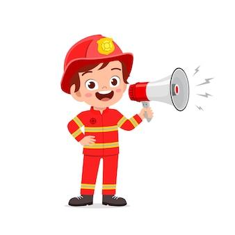 Felice carino ragazzino che indossa l'uniforme del pompiere e che tiene il megafono