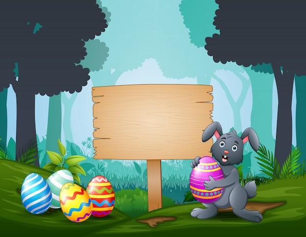 Coniglietto di pasqua felice con le uova di pasqua da un cartello di legno