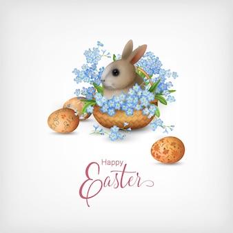 Biglietto di buona pasqua con cesto pieno di fiori primaverili, uova dipinte e simpatico coniglietto
