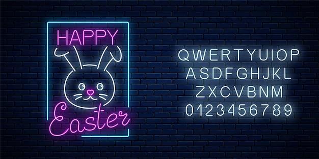 Insegna luminosa di pasqua felice con coniglietto e scritte con alfabeto in stile neon sul fondo del muro di mattoni scuri.