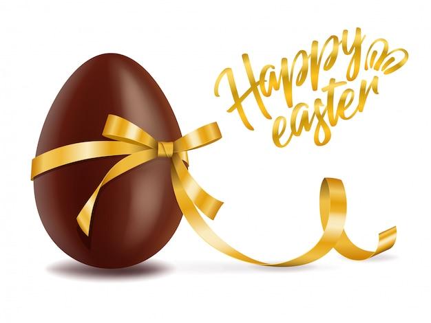 Saluto felice di pasqua, uovo di cioccolato con il nastro giallo