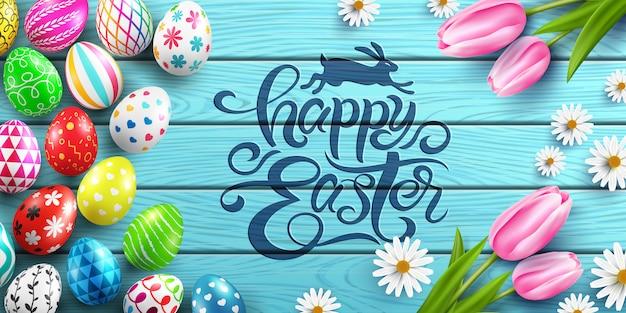 Manifesto e modello felici di pasqua con le uova di pasqua variopinte e fiore sulla tavola di legno.