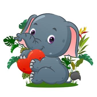L'elefante felice è seduto e tiene la bambola dell'amore sulla sua mano nel parco dell'illustrazione