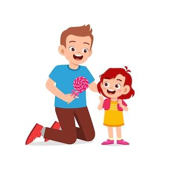 Il padre felice dà caramelle e dolci al suo ragazzo e alla sua bambina
