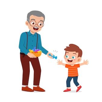 Il nonno felice dà cibo e caramelle ai nipoti