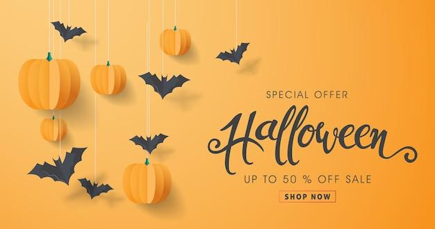 Felice calligrafia di halloween con pipistrelli di carta e zucche.
