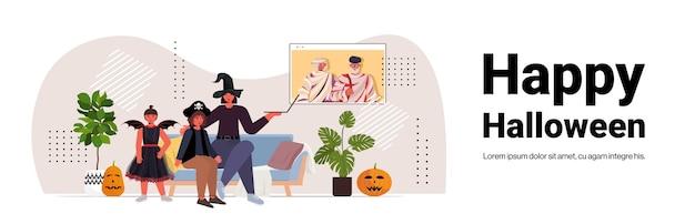 Famiglia felice di concetto di celebrazione di festa di halloween in costume che discute con i nonni durante la videochiamata