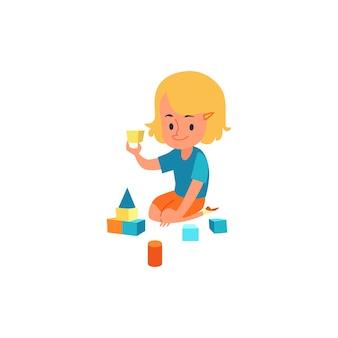 Bambino felice che si diverte con blocchi colorati, bambina che fa lo sviluppo del bambino e attività educativa che si siede sul pavimento con i giocattoli