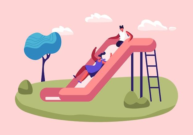 Ragazze felici dei bambini che hanno divertimento scorrevole sul parco giochi all'aperto.