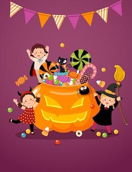 Bambini felici in costumi di halloween e una zucca piena di caramelle.