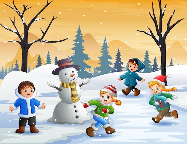Bambini felici che giocano all'aperto in inverno
