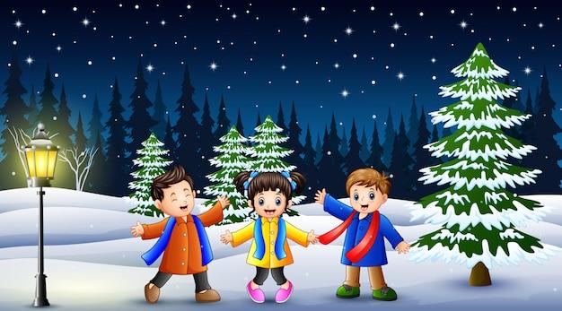 Bambini felici che giocano nel paesaggio invernale di notte