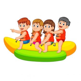 I bambini felici cavalcano sulla barca di banana Vettore Premium