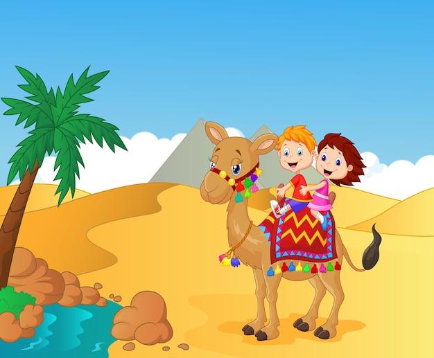 Bambini felici che guidano cammello