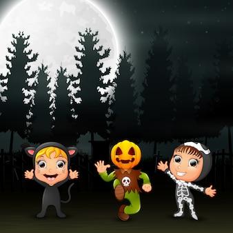 Bambini felici che indossano il costume di halloween nel giardino di notte
