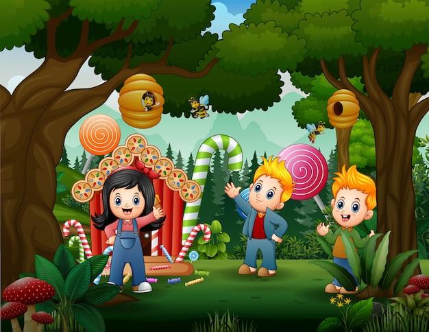Bambini felici con casa di caramelle nel paesaggio forestale