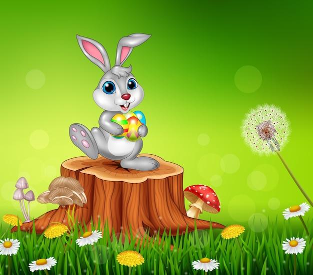 Piccolo coniglietto felice che tiene le uova di pasqua