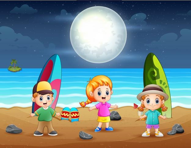 Bambini piccoli felici che giocano sulla spiaggia di notte