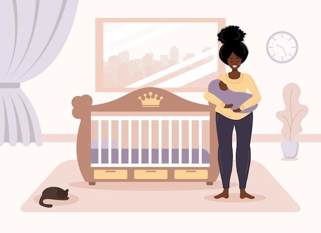 Maternità felice. la ragazza africana sta alla culla e tiene il bambino tra le braccia.